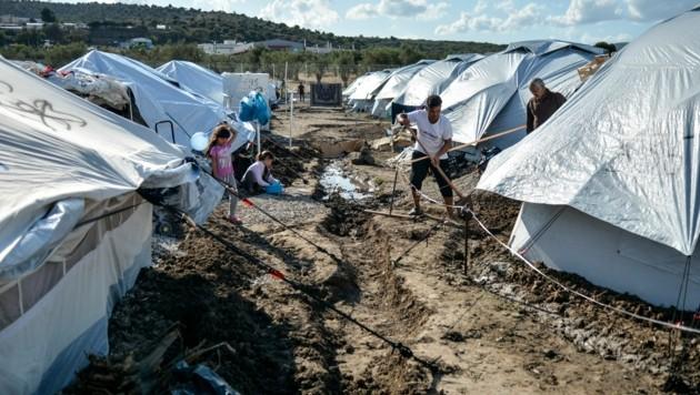 Migranten müssen im Ausweichlager Kara Tepe auf Lesbos Gräben schaufeln, damit Regen besser abrinnen kann. (Bild: AP)