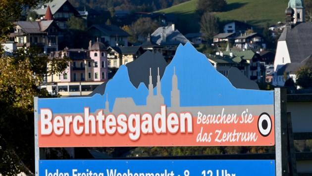 """Ein Schild mit der Aufschrift """"Berchtesgaden - Besuchen Sie das Zentrum"""" hängt vor der Kulisse der Ortschaft. (Bild: APA/dpa/Peter Kneffel)"""