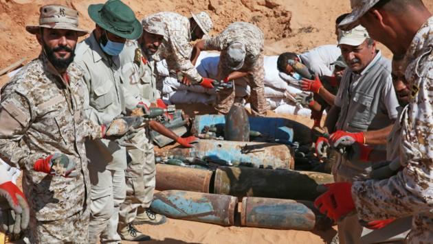Militärpersonal der von den Vereinten Nationen anerkannten Regierung bei der Zerstörung von Munition (Bild: APA/AFP/Mahmud TURKIA)