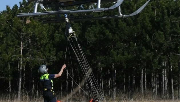 Ein Flightoperator der Flugpolizei befestigt einen Löschwasserbehälter unter dem Helikopter (Bild: Huber Patrick)
