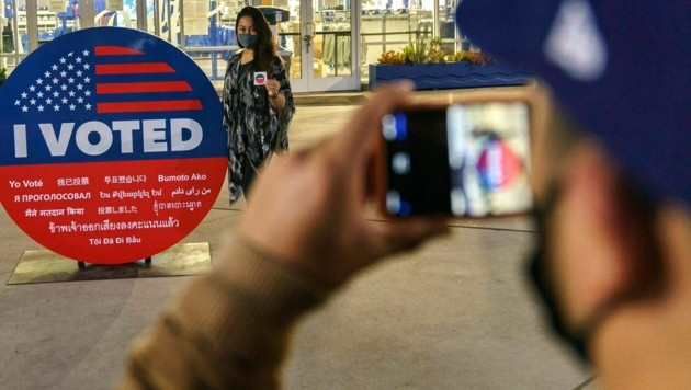 """Eine Wählerin lässt ein Foto mit einem """"Ich habe gewählt""""-Schild von sich schießen. (Bild: AP)"""