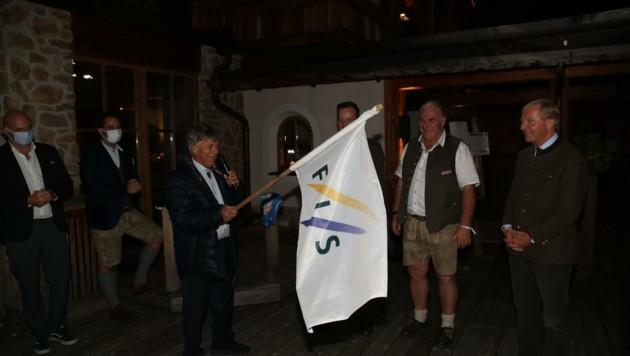 Die FIS-Fahne für den WM-Veranstalter wurde schon pro forma von ÖSV-Boss Schröcksnadel (li.) an Bewerbungsboss Gensbichler (mit Lederhose neben LH Haslauer) übergeben. (Bild: Tröster Andreas)