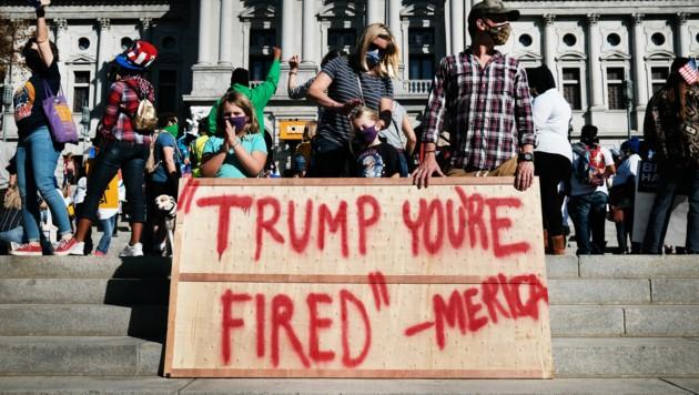 """""""Trump, du bist gefeuert"""", steht auf diesem Schild, das Demonstranten vor dem Kapitol in Harrisburg im US-Bundesstaat Pennsylvania aufgestellt haben. Jener Staat, der Biden letztlich zum Sieger der Präsidentschaftswahl machte. (Bild: AP)"""