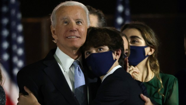 Joe Biden umarmt nach seinem Wahlsieg einen seiner Enkelsöhne. In seiner Siegesrede gedenkt der liebevolle Familienmensch auch seinem verstorbenen Sohn Beau. (Bild: Win McNamee/Getty Images/AFP)