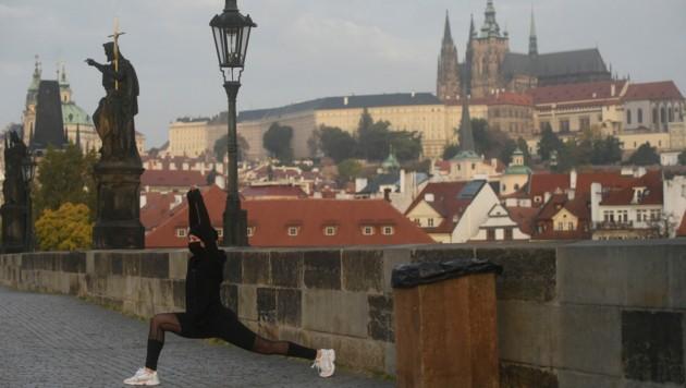 Eine Sportlerin auf der Karlsbrücke in Prag trägt auch beim Laufen vorschriftsmäßig eine Maske. (Bild: AFP )