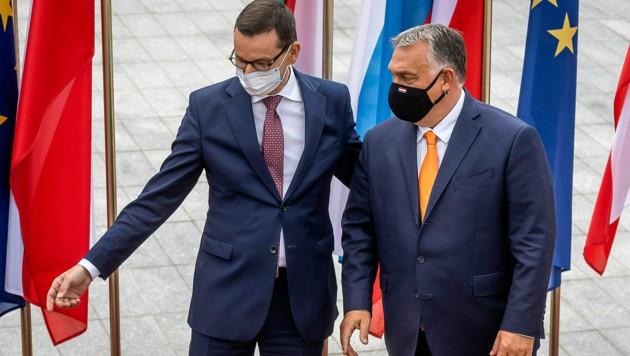 """Die Ministerpräsidenten Mateusz Morawiecki (Polen, li.) und Viktor Orban wollen sich eigenen Angaben zufolge nicht von der EU """"erpressen lassen"""". (Bild: APA/AFP/Wojtek RADWANSKI)"""