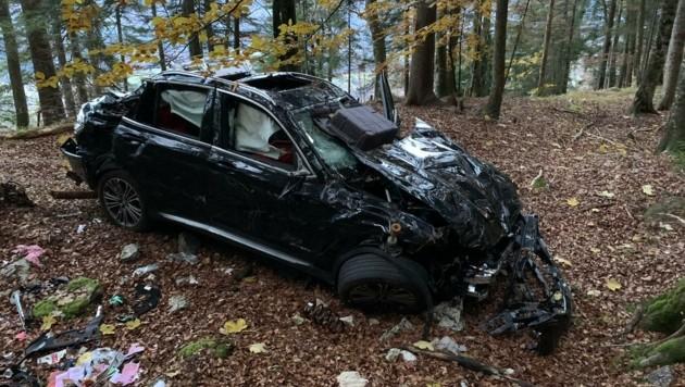 Das Unfallwrack liegt unter einer hohen Felswand im Wald. (Bild: Wallner Hannes)