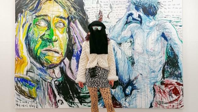 "Die Wiener Multi-Künstlerin Elke Silvia Krystufek mit Hidschab vor ihrem Acrylgemälde aus 2009 mit dem Titel: ""You don´t want to be one of those Picabias you say"". (Bild: Galerie Bernd Kugler)"