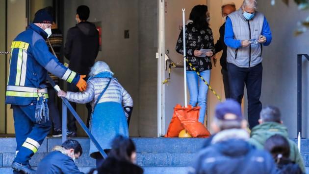 Sicherheitsleute achten auf den nötigen Mindestabstand in der Schlange. (Bild: AFP)
