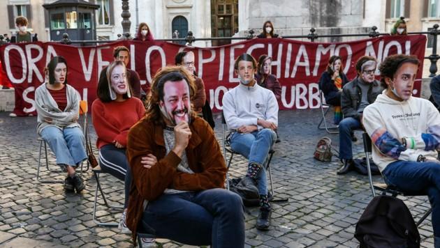 Studenten protestieren sitzend in Rom - sie tragen dabei Gesichter von Politikern als Maske. (Bild: LaPresse)