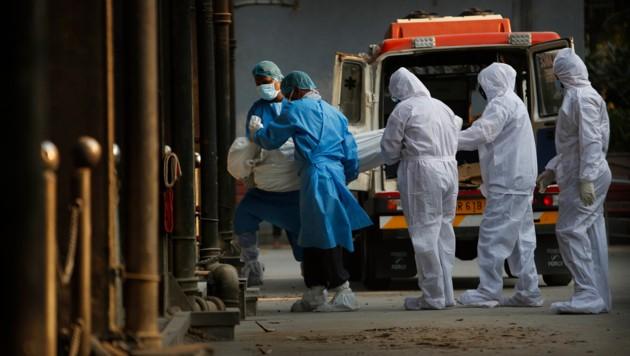 Verwandte und medizinisches Personal tragen den Körper eines Covid-19-Opfers ins Krematorium. (Bild: ASSOCIATED PRESS)