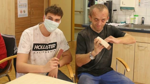 Jonas Atteneder mit dem Beschäftigten Simon Windischhofer beim Schleifen in der Holzwerkstatt. (Bild: Lebenshilfe Oberösterreich)