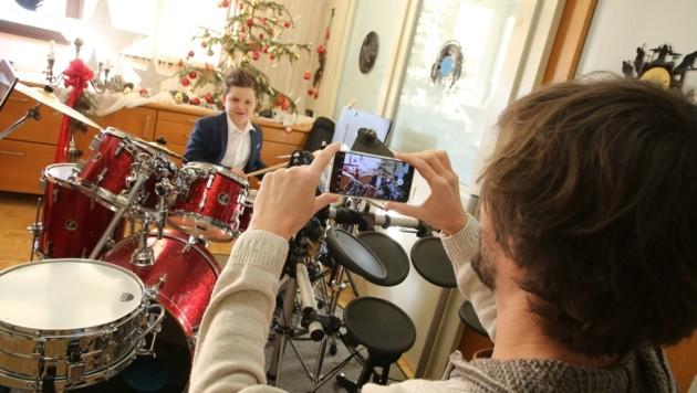Musikschuldirektor Matej Krevs zeigt mit Julian am Schlagzeug, wie die Videos entstanden. (Bild: Hronek Eveline)
