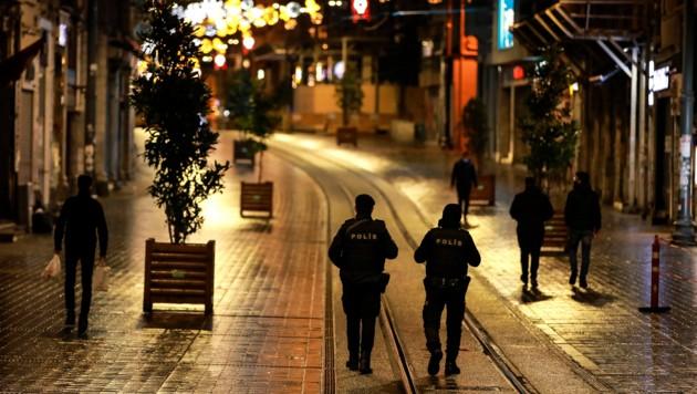 Polizisten kontrollieren die Ausgangssperren in einer Einkaufstraße in Istanbul. (Bild: Associated Press)