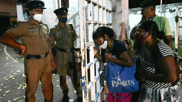 Menschen trauern vor einem Gefängnis um Angehörige, die bei der Revolte am Sonntag ums Leben kamen. (Bild: LAKRUWAN WANNIARACHCHI / AFP)