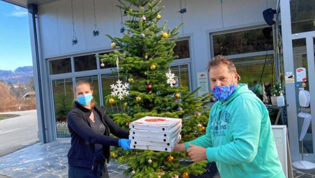 """""""PiPaPo""""-Mitarbeiterin Eva-Maria gibt Andreas fünf Pizzen mit, in Maria Rain wird noch mehr zum Abholen angeboten. (Bild: Christian Tragner)"""