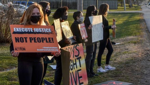 Junge Menschen protesterieren vor dem Gefängnis von Terre Haute in Indiana gegen die Hinrichtung von Brandon Bernard. (Bild: AP)