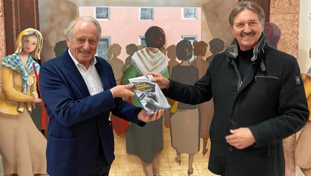 Herausgeber Günther Berghofer (li.) überreicht das erste Exemplar des druckfrischen Buches an Stadtchef Hans Lintner. (Bild: Berger Hubert)