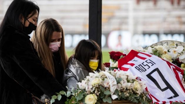 Die Ehefrau von Paolo Rossi, Federica Cappelletti (L) und die zwei Töchter des Paares am Sarg des Stars. (Bild: AFP/Marco Bertorello)