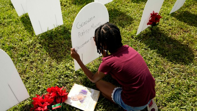 Eine Enkelin gedenkt ihrer infolge einer Covid-Erkrankung verstorbenen Großmutter auf einem symbolischen Friedhof für Corona-Opfer in Florida. (Bild: AP)