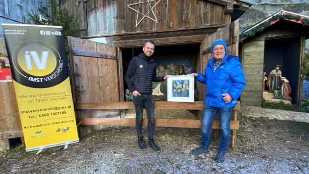 Daniel Seidner (li.) und Josef Gomig zeigen das Bild von Dietlinde Bonnlander, das bis 20. Dezember ersteigert werden kann. (Bild: imst verschenkt)