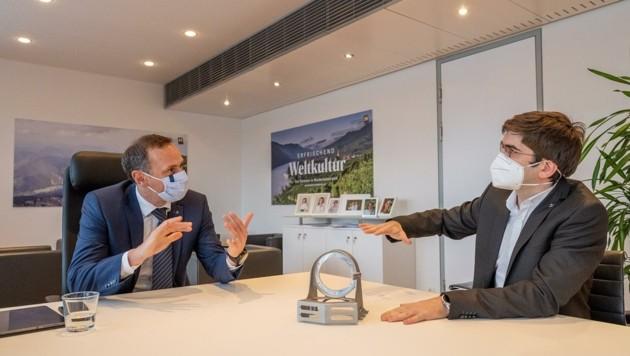 Wirtschaftslandesrat Jochen Danninger (links) lässt sich von Firmenchef Alexander Reissner Raumfahrttechnik erklären.