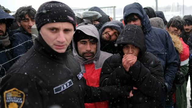 Im abgebrannten Lager Lipa gestrandete Migranten warten auf ihre Essensration. (Bild: AP)