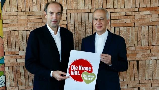 """""""Krone""""-Chef Dichand und """"Caritas""""-Präsident Landau (re.) mit einem gemeinsamen Hilfs-Logo (Bild: Jöchl Martin)"""