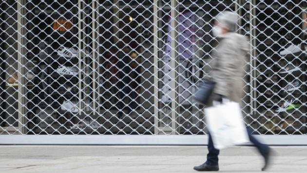Eine Frau mit einer Einkaufstasche geht an einem geschlossenen Geschäft in der Stuttgarter Königsstraße vorbei. Der Handel rechnet nicht mit einem raschen Ende der coronabedingten Ladenschließungen. (Bild: APA/DPA/TOM WELLER)