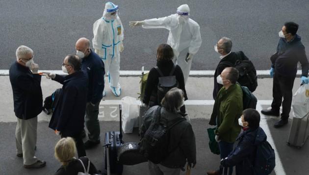 Das Expertenteam der WHO wurde bei der Ankunft von Gesundheitspersonal in Schutzausrüstung begrüßt. (Bild: AP)
