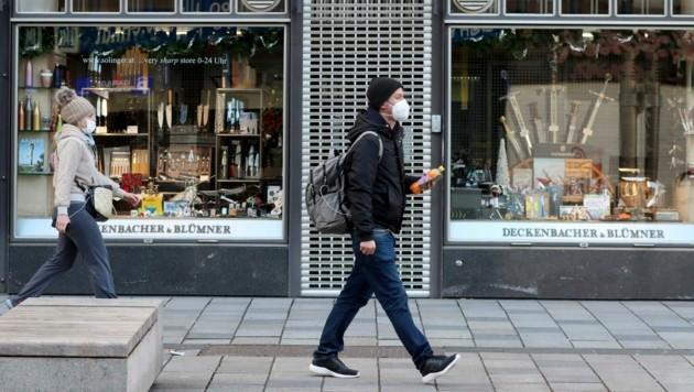 Mittlerweile ein gewohntes Bild in Österreich: Fußgänger gehen mit Mund-Nasen-Schutz an geschlossenen Geschäften vorbei. (Bild: AP)