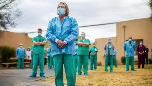 Mitarbeiter eines Krankenhauses in Tucson (Arizona) gedenken jener Menschen, die in Zusammenhang mit dem Coronavirus verstorben sind. (Bild: AP/Arizona Daily Star/Josh Galemore)