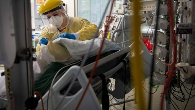 In Großbritannien stürmten Anhänger von Verschwörungstheorien rund um das Thema Coronavirus eine Intensivstation und wollten einen Covid-Patienten mitnehmen, der sich in kritischem Zustand befand. (Bild: AP)
