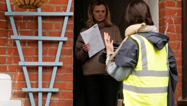 Eine freiwillige Helferin bringt einer Londonerin ein Heim-Testkit. (Bild: APA/AFP/NIKLAS HALLE'N)