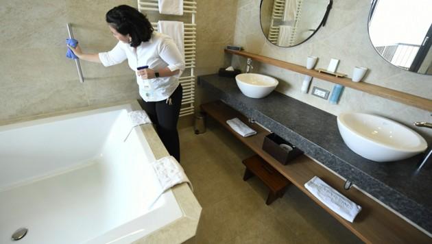Eine Hotelangestellte bei den letzten Vorbereitungen in einem Gästezimmer. (Bild: APA/ROBERT JAEGER)