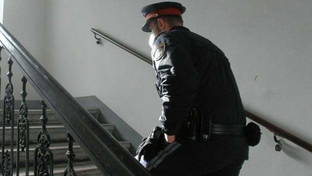 Ein Polizist auf den Weg in jene Wohnung, in der die 28-Jährige leblos aufgefunden wurde. (Bild: Andi Schiel)