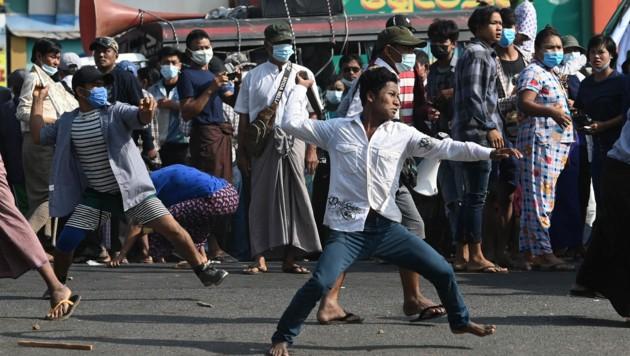 Unterstützer des Militärs werfen Steine auf Demonstranten (Bild: AFP)