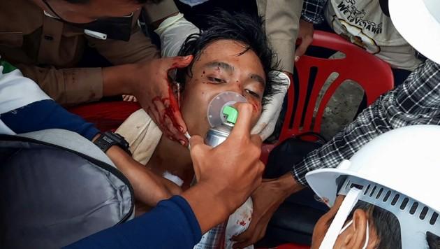 Nach einem Zusammenstoß mit Sicherheitskräften wird ein verletzter Demonstrant medizinisch versorgt. (Bild: APA/AFP/AFPTV/DAKKHINA INSIGHT/Handout)