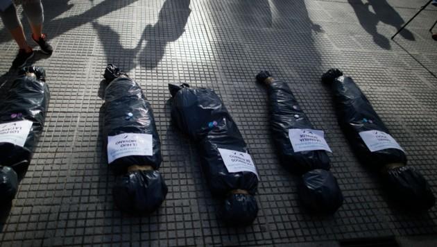 """Leichensäcke repräsentierten an Corona verstorbene Menschen. Darauf die Nachricht: """"Ich habe auf eine Impfung gewartet, doch sie wurde Albertos (der Präsident Argentiniens, Anm.) Freunden verabreicht."""" (Bild: AP Photo/Natacha Pisarenko)"""