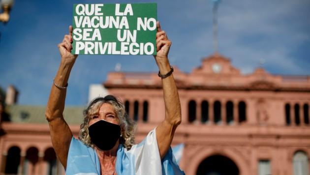 """""""Impfungen sollten kein Privileg sein"""", fordert diese Demo-Teilnehmerin am Samstag. (Bild: AP Photo/Natacha Pisarenko)"""