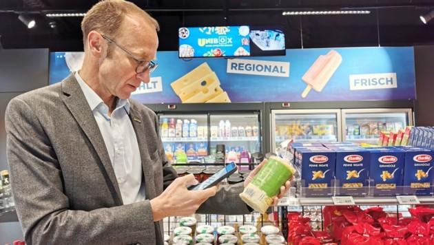 Unimarkt-Chef Andreas Haider beim Testlauf in Enns: Die Produkte scannt er mit dem Smartphone, bezahlt wird in der App. (Bild: Barbara Kneidinger)