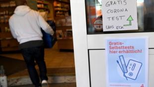 Ein Hinweis auf kostenlos erhältliche Covid-19-Antigen-Heimtests an einer Apotheke in Wien (Bild: APA/Roland Schlager)