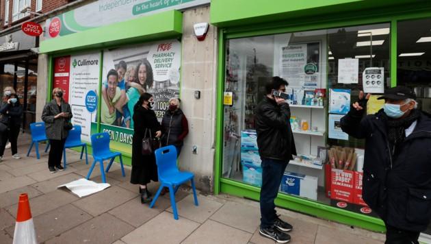 Menschen warten außerhalb einer Apotheke in London auf ihre Corona-Teilimpfung. (Bild: AP)