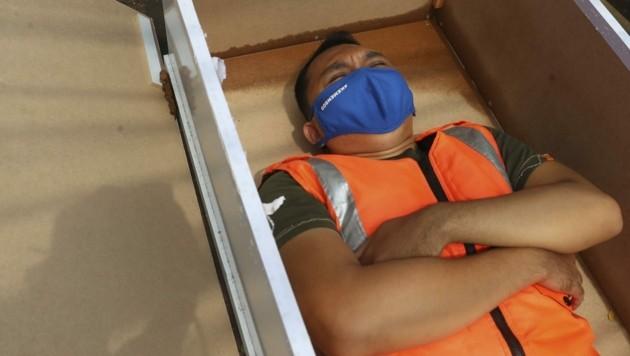 Masken-Verweigerer müssen in Indonesien im Sarg liegen. (Bild: AP)