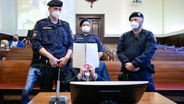 Der Angeklagte versteckte vor Prozessbeginn sein Gesicht (Bild: Alexander Schwarzl)