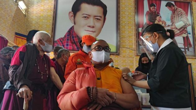 Ein Mönch wird in Bhutan vor einem Porträt von König Jigme Khesar Namgyel Wangchuck geimpft. (Bild: APA/AFP/Upasana DAHAL)