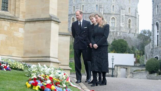 Prinz Edward, Lady Louise Windsor und Sophie, die Countess von Wessex, betrachten am Vortag des Begräbnisses vor der St George's Chapel auf Schloss Windsor Blumen, die im Gedenken an Prinz Philip niedergelegt wurden. (Bild: APA/AP)