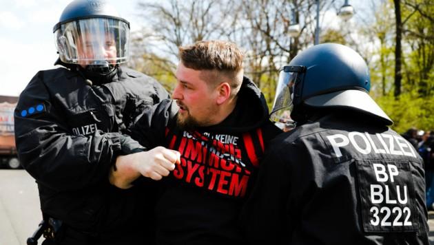 Tausende Gegner der Corona-Politik der Merkel-Regierung protestierten lautstark gegen das neue Gesetz. Die Polizei nahm Dutzende Demonstranten fest. (Bild: AP)