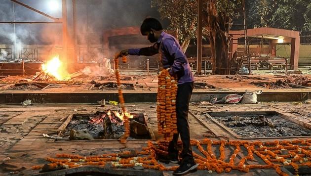 Ein Trauernder legt Blumenkränze ab. Auf dem Subkontinent wütet derzeit die Pandemie. (Bild: SAJJAD HUSSAIN)