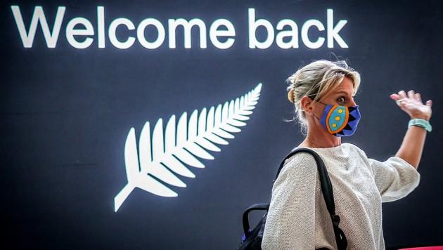 Eine aus Neuseeland zurückgeflogene Passagierin auf dem Flughafen von Sydney (Bild: APA/AFP/David Gray)